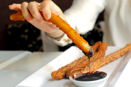 Female hand enjoying dipping Churros to dark chocolate sauce photo
