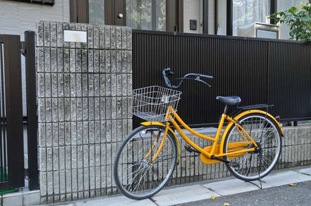 Yellow classical bicycle parked on the street photo