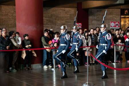 yat sen: Taipei Taiwan  February 3 2015: Guards are changing at Sun Yat Sen Memorial hall in Taipei Taiwan. This photo is taken in the morning shift inside the central section of the hall. The soldier are carrying traditional rifles with blue flag and marching pas