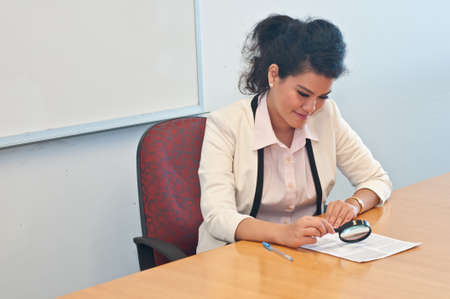 to examine: Business woman examine contract details by magnifier Stock Photo
