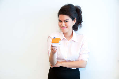 and real estate: Business woman hold house toy model on white background
