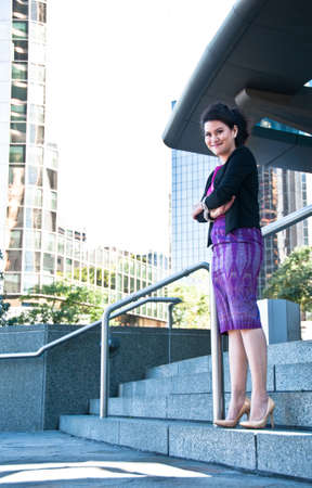 businesswoman suit: Asian business woman with Thai silk purple dress stand in front of office buildings
