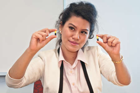 compare: Woman compare two medicine capsules with hands