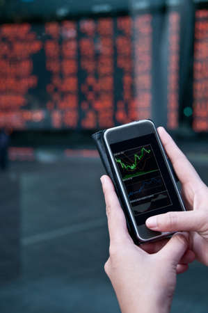 derivative: Trading stock on mobile near exchange board