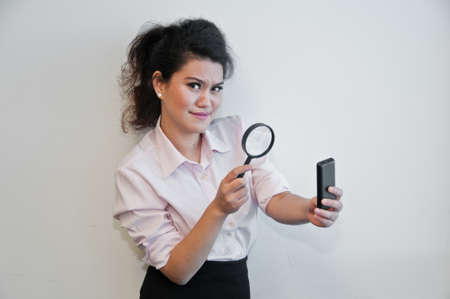 Business woman examine mobile phone by magnifier Stock Photo