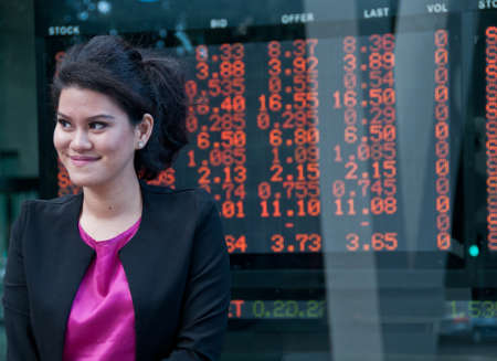 stock market exchange: Business woman stand near stock market exchange board