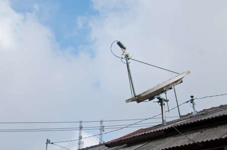satelite: Modern high technology satellite on a roof with cloudy sky