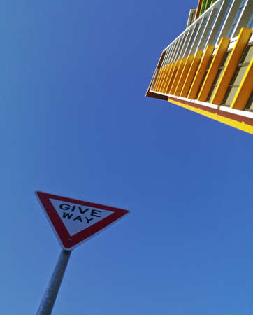 Modern high rise yellow apartment and blue sky with Give Way sign