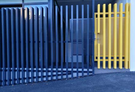 Moderne blauwe en gele metalen hek van een appartement