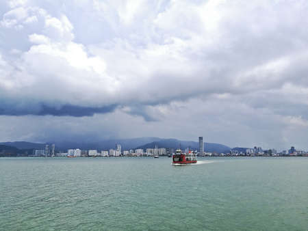 Penang and Malaysia Mainland sea channel with red ferry