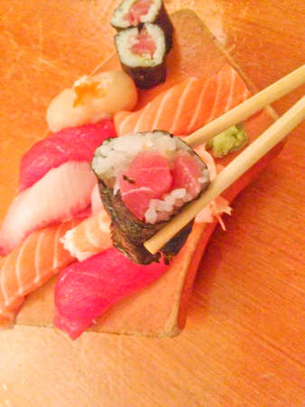 Mixed fresh Japanese sushi platter served on wooden plate and eat with chopsticks