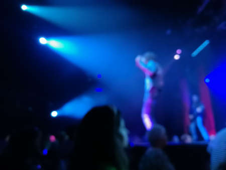 Defocused abstract blurred scene of musical light performance in a concert on stage with crowd Stock Photo