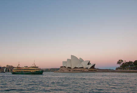 SYDNEY, AUSTRALIA - MAY 5, 2018: Sydney Opera House with famous Sydney city ferry in late afternoon and twililght sky. Editorial