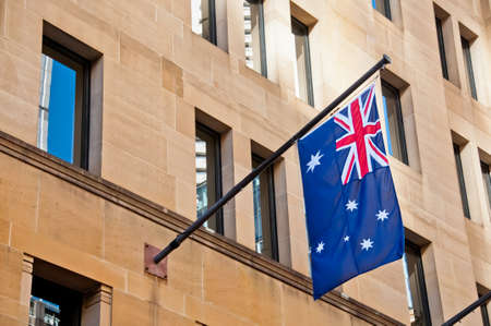 Flag of Australia hang from a sandstone building