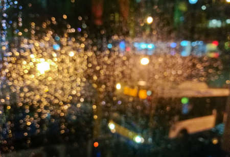 Defocused golden light sparkle scene of city bus in rainy night