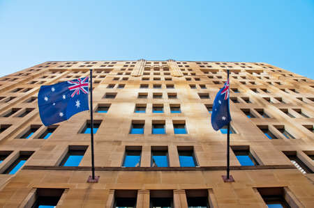 Two Australia flags hanging from a sandstone building