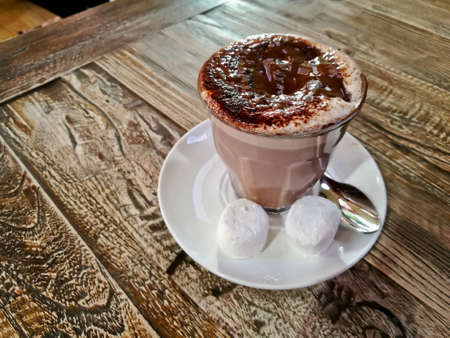 Black and white hot creamy mocca chocolate coffee served on a wooden table with two marshmallow