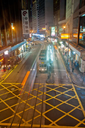 HONG KONG, HONG KONG SAR - NOVEMBER 17, 2018: Light blur motion scene of tram and traffic in central Hong Kong at night. There are many pedestrians on the street.
