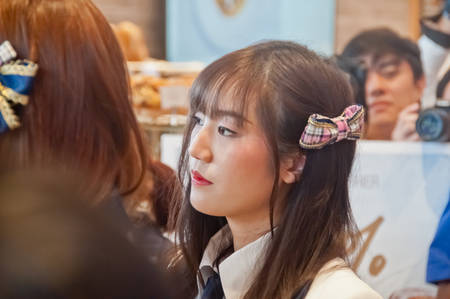 BANGKOK, THAILAND - NOVEMBER 23, 2018: Dusita Kitisarakulcha (Natherine), a member of Thai Idol girl group BNK48, looks with curiosity to see  fanclub in Gontran Cherrier bakery grand opening public event. There are many fanclub takes photos of her in the