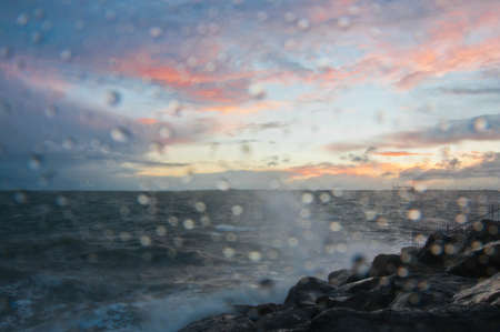 Dramatic splashing ocean wave in the evening with twilight sky in Winter at breakwater at St Kilda pier in Melbourne Australia