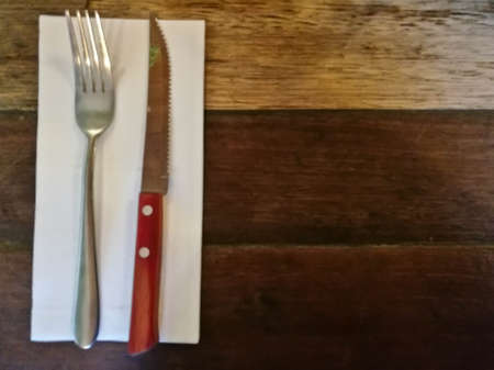 Top view of silver fork and knife on tissue paper on wooden classic table
