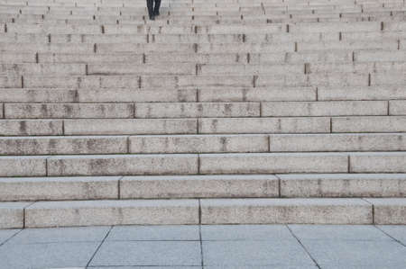 Feet of a man stepping up grey concrete stone stairs upwards Stock Photo