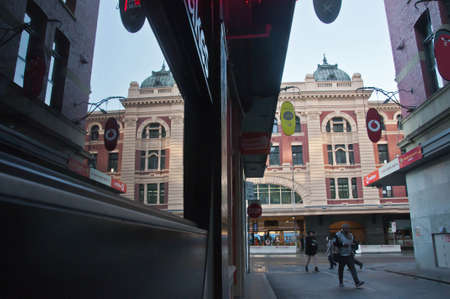 MELBOURNE, AUSTRALIA - JULY 29, 2018: Flinders street train station scene looks from Degrave laneway in Melbourne city center. There are tourists walks on the laneway in the morning.