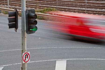 Moving blurred red car with green traffic light pole and no u-turn sign