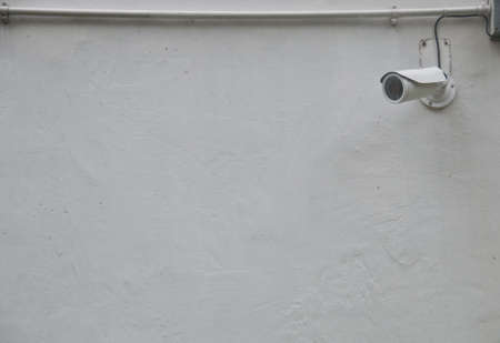 White CCTV security camera with wired data line attached on a white concrete wall