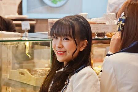 BANGKOK, THAILAND - NOVEMBER 23, 2018: Nannaphas Loetnamchoetsakun (Mewnich), a member of Thai Idol girl group BNK48, smiles and laught at the  fanclub in Gontran Cherrier bakery grand opening public event. There is another band member and waitress stand