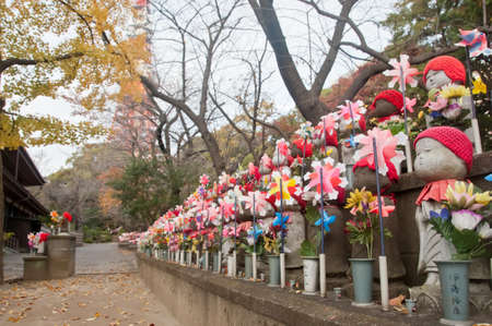 TOKYO, JAPAN - DECEMBER 1, 2018: Scene of wind turbine papers to worship souls of children in the back park of Zojo-ji Buddhist famous temple built from 1622. There is nobody in the photo. There is Tokyo Tower nearby the temple.