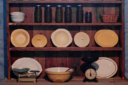 Vintage kitchenware and utensil on brown wooden cupboard in a house Stock Photo