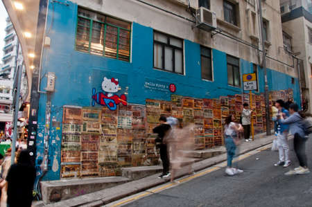 HONG KONG, HONG KONG SAR - NOVEMBER 17, 2018: Scene of blurred motion of moving people with Hong Kong famous street graffiti painting. The painting is Tong Laus on Graham Street in Soho area. Tong Laus is a building type in Hong Kong. There are many peopl