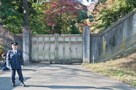 TOKYO, JAPAN - DECEMBER 1, 2018: A Japanese police guard stands in front of internal park gate with a man sits inside the Japanese Royal Imperial Palace. Editorial