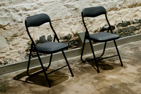 Two modern black chairs in a strong rock prison cell