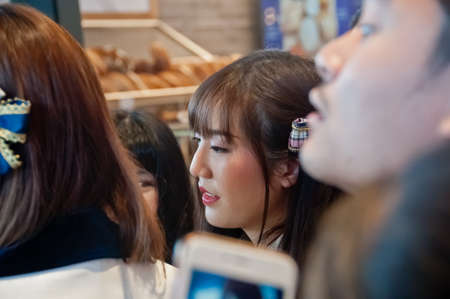 BANGKOK, THAILAND - NOVEMBER 23, 2018: Dusita Kitisarakulchai (Natherine), a member of Thai Idol girl group BNK48, looks with curiosity to see  fanclub in Gontran Cherrier bakery grand opening public event. There are many fanclub takes photos of her in th