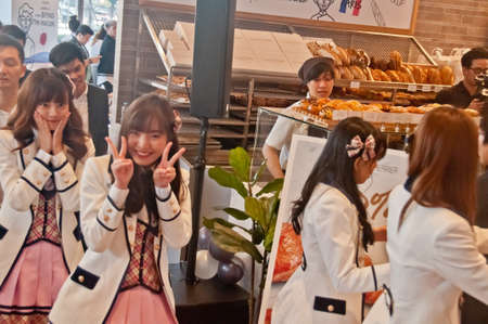 BANGKOK, THAILAND - NOVEMBER 23, 2018: Dusita Kitisarakulchai (Natherine), a member of Thai Idol girl group BNK48, show Victory signs by 2 hands to greet  fanclub in Gontran Cherrier bakery grand opening public event. There are other band members and staf