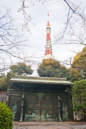TOKYO, JAPAN - DECEMBER 1, 2018: Dark green metallic gate of a park of Zojo-ji Buddhist famous temple built from 1622. There is nobody in the photo.  There is Tokyo tower at the back of the temple.