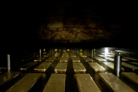 Many gold bars kept in the dark of a safe strong room