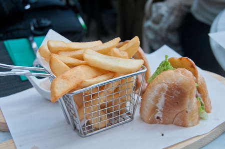 Crispy golden hand cut chips deep fried with French handmade sandwich served on white paper Imagens