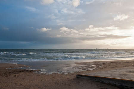 Beautiful blue cloudy sky with strong high tide wave of sea ocean creep to golden beach and wooden pavement in Melbourne Australia Foto de archivo