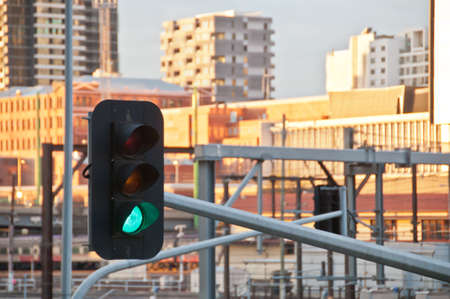 Green light traffic signal with contemporary train station background Banco de Imagens