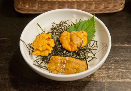 Premium supreme delicious fresh from the sea 3 types of uni sea urchin sashimi from Tokyo, Mexico, Canada on top of warm steamed rice with crispy grilled seaweed.