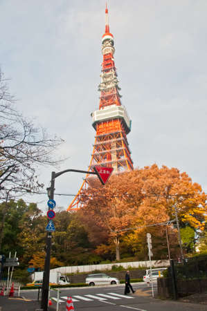 TOKYO, JAPAN - DECEMBER 1, 2018: Famous Tokyo Tower situates in the central Tokyo in the morning. The tower is a communications and observation tower with around 330 metres tall and was built in 1958. There is a man walks on the street.