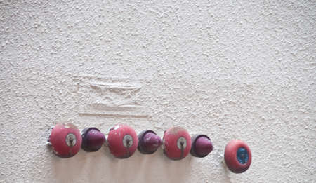 Many red fire alarm bells attached on a building wall 写真素材