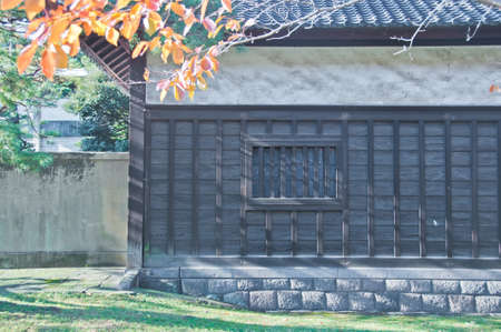 Traditional Japanese wooden house with Autumn red orange green trees leaves