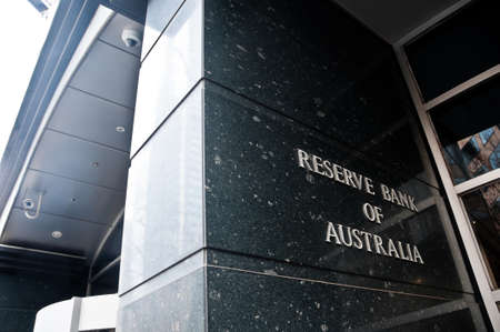 MELBOURNE, AUSTRALIA - JULY 26, 2018: Reserve Bank of Australia name on black granite wall in Melbourne Australia with a reflection of high-rise buildings. The RBA building is located at 60 Collins St, Melbourne VIC 3000 Australia. 報道画像