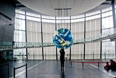 TOKYO, JAPAN - DECEMBER 2, 2018: Miraikan National Museum of Emerging Science and Innovation. The Geo-Cosmos floating earthsphere displays rendition of earth surface by 10 million pixels of organic LED panels. There are  visitors taking photos and sit on