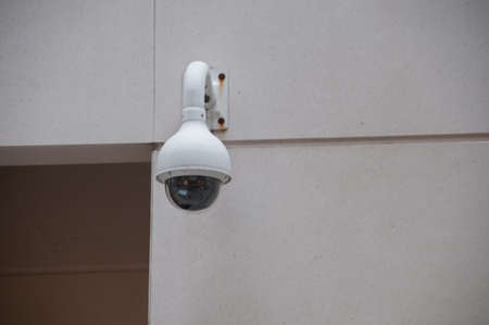 Security CCTV dome camera attached to a white wall near the door