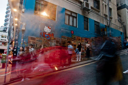 HONG KONG, HONG KONG SAR - NOVEMBER 17, 2018: Scene of blurred motion of moving people with Hong Kong famous street graffiti painting. The painting is Tong Laus on Graham Street in Soho area. Tong Laus is a building type in Hong Kong. There are many peopl 写真素材 - 152969665